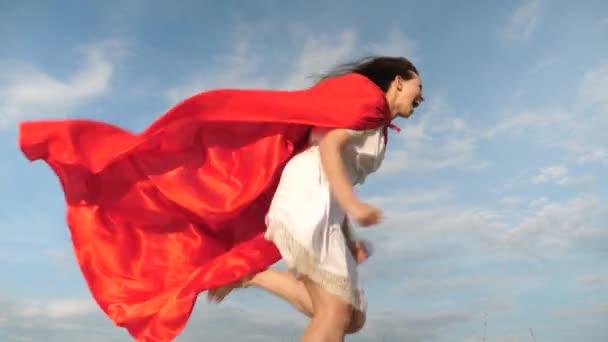 boldog superhero lány futni és nevetni piros köpenyt, köpenyt, csapkodott a szélben. Vidám, fiatal nő játszik a szuper hős. lány álma válhat egy szuperhős. lány-az álmok egy piros köpenyt kifejezésben.