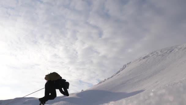 tři Alpenists v zimě vylézt lano na hoře. Cestovatele šplhat lana na jejich vítězství sněhu do kopce v silném větru. Turisté v zimě společně pracovat jako tým, překonávání překážek