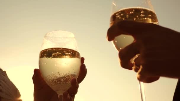 Champagner funkelt und schäumt in Sonne. paar in Liebe Hintergrund des Sonnenuntergangs Weingläser mit Sekt festhalten. Close-up. Teamarbeit der liebende Paar. Erfolg und Sieg zu feiern. Slow-motion