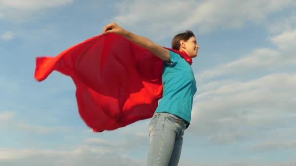 gyönyörű lány szuperhős állva a mezőben egy piros köpenyt, köpenyt, csapkodott a szélben. Lassú mozgás. lány álma válhat egy szuperhős. fiatal lány állt egy piros köpenyt kifejezés az álmok