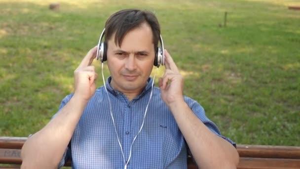schöner junger Mann, der mit Kopfhörern Musik von seinem Smartphone hört, draußen im Park auf einer Bank in der Mitte Europas tanzt