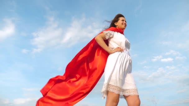 bella ragazza sogna di diventare un supereroe. sexy supereroe ragazza in piedi sul campo in un mantello rosso, mantello svolazzanti nel vento. Rallentatore. giovane ragazza in un sogno rosso del capo espressione