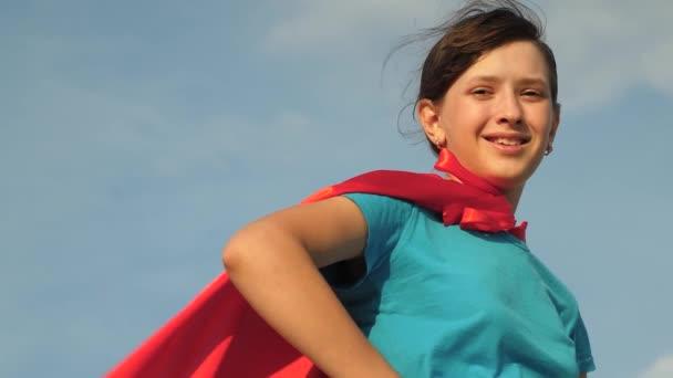 lány álma válik szuperhős. gyönyörű lány szuperhős állva területén piros köpenyt, köpeny csapkodott a szél. Lassított. Közeli. fiatal lány állt a piros köpenyt kifejezése álmok.