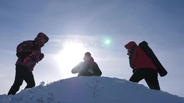 Cestovatelé se setkali na vrcholu úspěchu. Turisté přicházejí na vrchol zasněženého kopce a radili se z vítězství na pozadí žlutého západu slunce. týmové práce a vítězství. Týmová práce osob v obtížných podmínkách