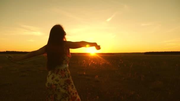 Šťastná dívka poslouchá hudbu a tančí v paprscích nádherného západu slunce v parku. mladá dívka ve sluchátkách a s smartphone v letu pod paprsky teplého slunce. Zpomaleně.