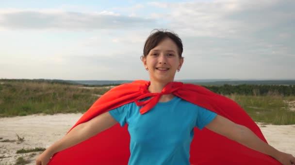 fiatal lány álma egyre szuperhős. gyönyörű lány szuper hős fut át a területen piros köpeny előtt kék eget és mosolyog lassított. boldog tini lány megy piros köpenyt kifejezése álmok.