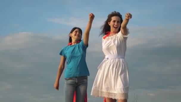 Anya és lánya játszik szuperhősök egy piros köpenyt. boldog család játszik a szuperhősök. Anya és gyermeke tesz vörös köpeny egy maskara. boldog család nevetett