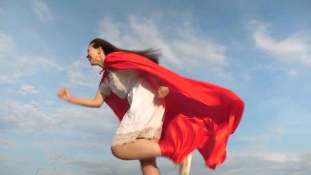 Vidám fiatal nő játszik a szuperhős. boldog szuperhős lány futni és nevetni piros köpenyt, köpeny csapkodott a szél. lány álma válik szuperhős. lány egy piros köpenyt kifejezése álmok.
