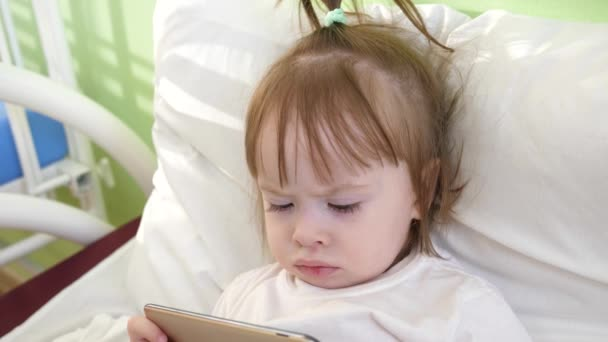 A small child is watching cartoons on a smartphone. kid playing on the phone in bed. little girl playing with a tablet on the bed.