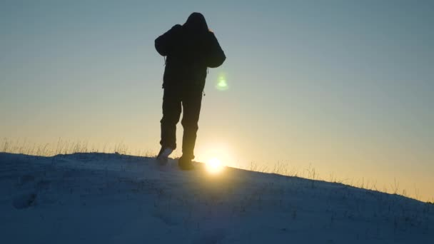 the traveler goes to victory overcoming difficulties. The traveler rises on a snowy hill in the rays of the sun. tourist goes on a snowy mountain to the top, at sunset. Alpenist travels hiking.