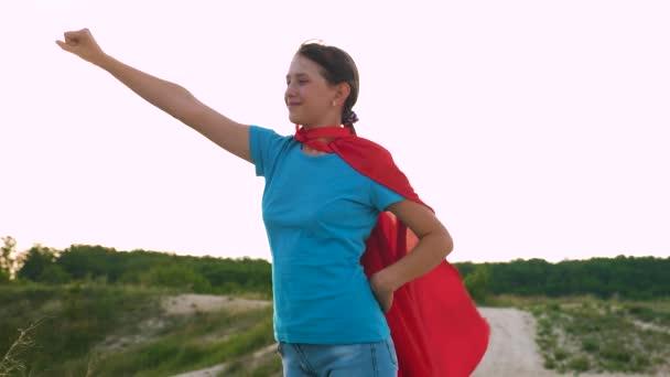 fiatal lány sétál egy piros köpenyt kifejezés az álmok. lány álma válhat egy szuperhős. gyönyörű lány szuperhős állva a mezőben egy piros köpenyt, köpenyt, csapkodott a szélben. Lassú mozgás.