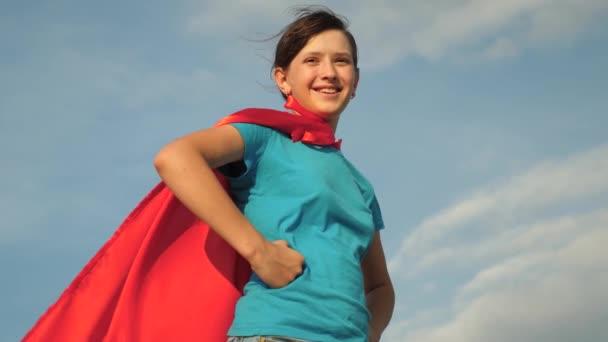 ragazza di supereroe ragazza adolescente in piedi sul campo in mantello rosso, mantello svolazzanti nel vento. Rallentatore. primo piano. ragazza sogna di diventare un supereroe. giovane ragazza in piedi in un mantello rosso espressione di sogni.