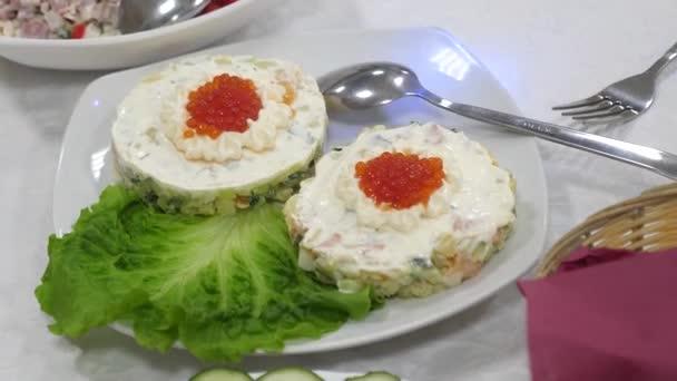 Sendviče s červeným kaviárem a zelený salát na talíři. Slavnostní jídelní stůl. lahodné jídlo na stole.