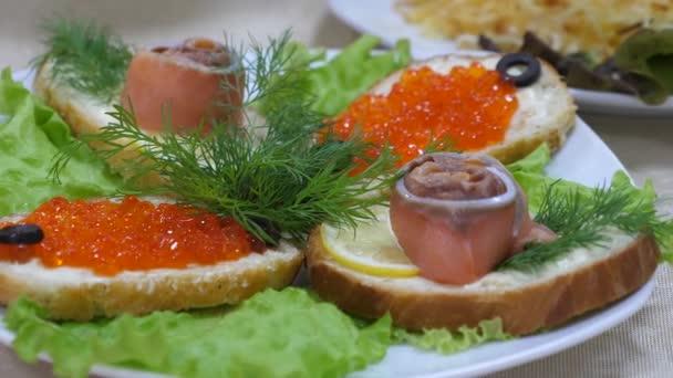Sendviče s červeným rybím a červeným kaviárem a Dill na plátu a na prostěradli. Slavnostní jídelní stůl. lahodné jídlo na stole.