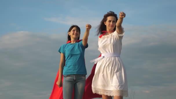 csapatmunka szuperhősök. két lány piros köpeny szuperhősök áll ellen a kék eget, a szél kinyílásakor egy köpenyt. Anya és lánya játszani szuperhősök. boldog családi koncepció.