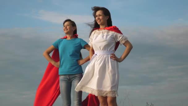 two girls in red cloaks of superheroes stand against a blue sky, the wind inflates a cloak. Mom and daughter play superheroes. happy family concept