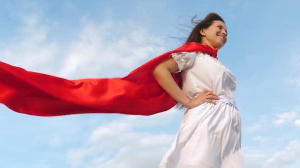gyönyörű lány álma válás szuperhős. szexi szuperhős lány állt a pályán egy piros köpenyt, köpenyt csapkodott a szél. Lassított. a fiatal lány egy vörös-foki álom kifejezés