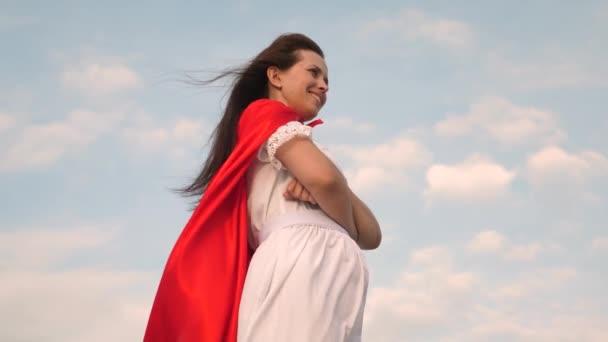 szuperhős lány állt a pályán egy piros köpenyt, köpenyt csapkodott a szél. Közeli. lány álma válik szuperhős. a fiatal lány egy vörös-foki álom kifejezés