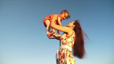 mother throw her daughter up to blu sky. slow motion filming. Mom plays with small child in her arms against sky. happy family playing in evening against sky. mother throws up baby, baby smiles
