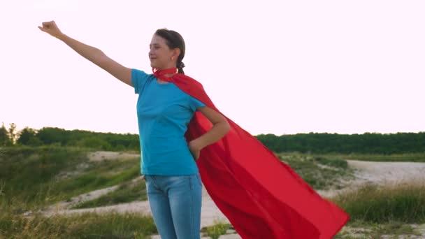 bella ragazza gioca in supereroe, in piedi sul campo in un mantello rosso, mantello svolazzanti nel vento. giovane ragazza cammina in unespressione mantello rosso di sogni. ragazza sogna di diventare un supereroe. Rallentatore.