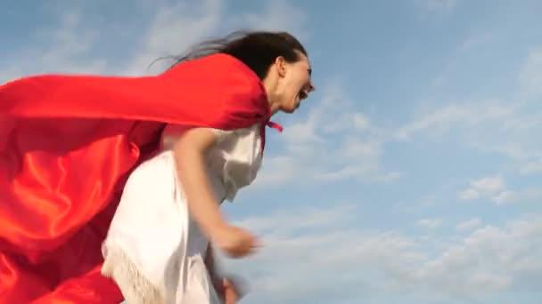 vicces szuperhős lány futni, és nevetni piros köpenyt, köpeny csapkodott a szél. Vidám fiatal nő játszik a szuperhős. lány álma válik szuperhős. lány egy piros köpenyt kifejezése álmok.