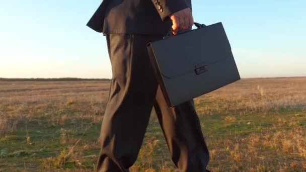 A businessman goes to work in the morning with a briefcase through the park. man in business suit with black briefcase in hand walks in the park. close-up.
