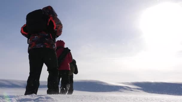 three alpinist tourists follow each other in the snowy desert. team work and victory. team of business people go to victory and success. teamwork of business people.