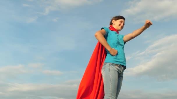 lány álmai egyre szuperhős a kék eget. fiatal lány állt piros köpenyt kifejezése álmok. gyönyörű lány szuperhős állva területén piros köpenyt, köpeny csapkodott a szél. Lassú