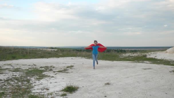 A fiatal lány arról álmodik, hogy szuperhős lesz. Boldog lány szuperhős fut át mező piros köpenyben előtt kék ég és mosolyog. Lassított felvétel. boldog tini lány megy piros köpeny kifejezése álmok
