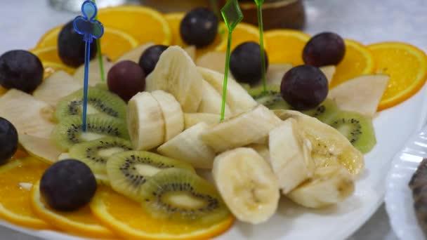 banai, pomeranče, hrozny, kiwi nakrájené, těsné. na stole lahodné jídlo. Čerstvý ovocný talíř na slavnostním jídelním stole. Rozmanité nakrájené ovocné špízy na talíři.