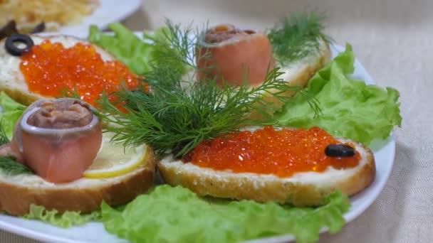 na stole lahodné jídlo. Sendviče s červeným rybím a červeným kaviárem a Dill na plátu a na prostěradli. Slavnostní jídelní stůl.