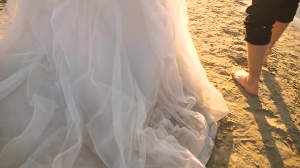 man and girl travel on the beach. close-up. bride in a white dress and the groom barefoot walking on the water on the river bank. Slow motion. loving couple walks on the summer beach.