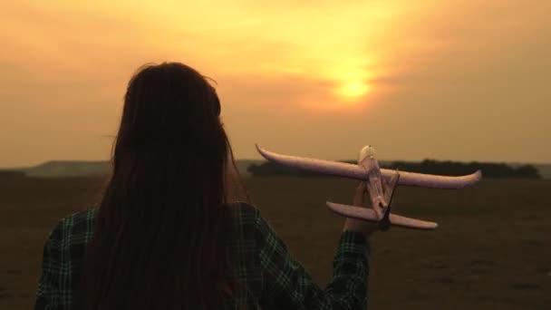 Boldog lány fut egy játék sík naplementekor a pályán. A koncepció egy boldog történet. gyermek játék játék repülőgép. Lány álma repül, és válik egy pilóta. tinédzser azt akarja, hogy a pilóta és az űrhajós