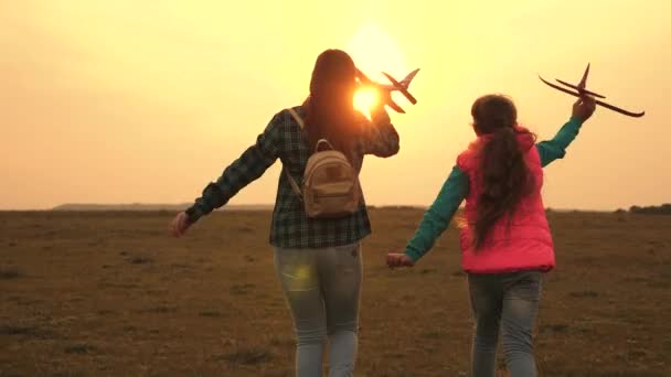 teenagers want to become pilot and astronaut. Happy girls run with toy plane at sunset on field. concept of a happy childhood. child playing toy airplane. Girls dream of flying and becoming a pilot.