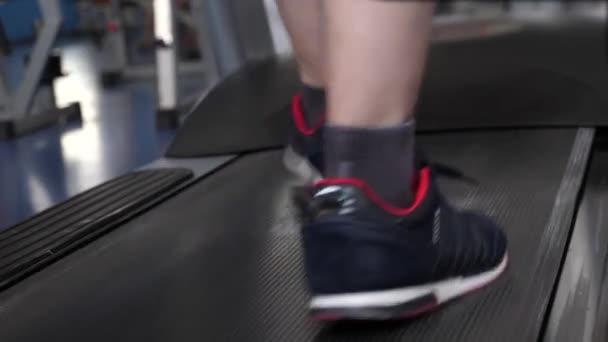 Fitness-Club-Mann beschäftigt sich mit dem Gehen. Nahaufnahme des Fußes. Stärkung der Beinmuskulatur durch Gehen. Herz-Kreislauf-Belastung. Ein Mann trainiert auf einem Laufband. Gehen in der Turnhalle. Sport-Lifestyle-Konzept. Gewichtsverlust im Fitnessstudio.