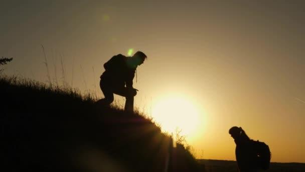 Reisender Mann reicht einem Mädchen, das auf einen Hügel klettert, die Hand. Reisende erklimmen händchenhaltend die Klippe. Teamwork der Geschäftsleute. glückliche Familie im Urlaub. Touristen umarmen sich auf dem Gipfel des Berges