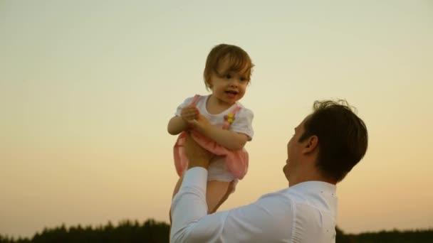 Apja játszik a lányával a parkban. Apa veti fel a baba az égen. boldog gyermekkori gyermek szüleivel. Apa dobta a gyerek magas. A boldog család koncepciója.