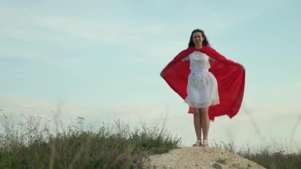 vicces és vicces nő játszik hős egy köpenyt vörös köpeny. lány álma válik szuperhős. gyönyörű szuperhős lány állt a pályán egy piros köpenyt, köpenyt csapkodott a szél.