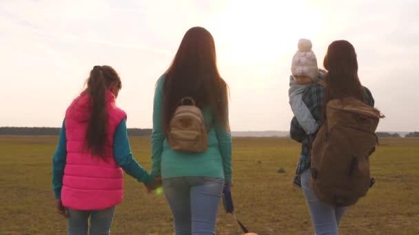 glückliche Familie mit Kindern reisen mit Rucksäcken. Teamwork einer engen Familie. Mutter, kleines Kind, Töchter und Haustiere Touristen. das Konzept eines sportlichen Familienurlaubs in der Natur.