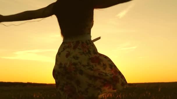 sexy Mädchen Musik hören und tanzen in den Strahlen eines schönen Sonnenuntergangs gegen den Himmel. Junge Mädchen mit Kopfhörern und Smartphone wirbeln im Flug unter den Strahlen eines warmen Sonnenuntergangs. Zeitlupe.