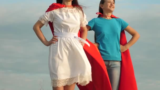 két lány piros köpeny a szuperhősök állni ellen kék eget, a szél fújja a köpenyt. Anya és lánya játszani szuperhősök. boldog családi koncepció