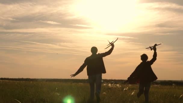 Két lány játszani egy játék sík naplementekor. Gyermekek a háttérben a nap egy repülőgép a kezében. Sziluettje gyerekek játszanak a gépen. Álmok-ból repülés. Boldog gyermekkori koncepció