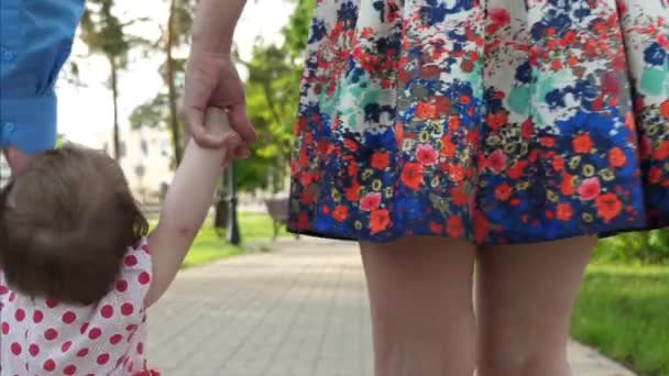 father and little daughter and mother go and hold hands. little baby learning how to walk with mom and dad. happy family walking in summer Park. children and parents.