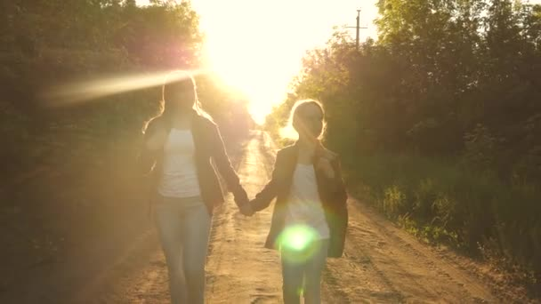 children travelers. teen girls travel and hold hands. Hiker Girl. girls with backpacks are on the country road in the sun. concept of sports tourism and travel.