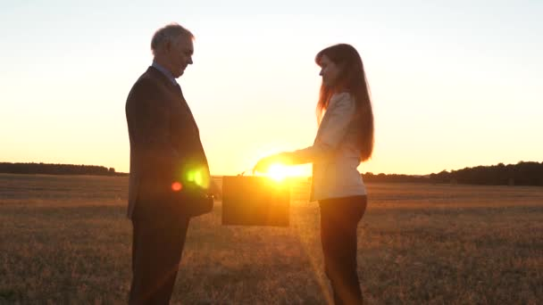 farmers man and woman made a deal. businessman and businesswoman shaking hands in glow of the sunset. Business woman passes briefcase with documents to businessman.