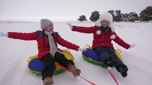 Glückliche Kinder rodeln im Winter im Schnee und winken mit den Händen. Kinder rutschen auf einer Röhre auf Schnee und lachen und jubeln. Mädchen spielen in den Weihnachtsferien im Winterpark. Zeitlupe