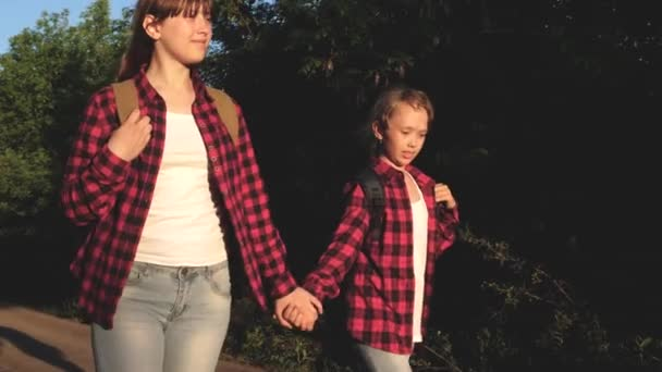 teen girls travel and hold hands. Hiker Girl. children travelers. girls with backpacks are on the country road in the sun. concept of sports tourism and travel.