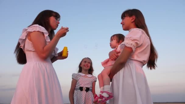 Töchter und Mutter blasen bei Sonnenuntergang Blasen im Park. zeitlupe. Glückliche Mutter spielt mit Kindern blasen Seifenblasen. glückliches Familienkonzept. Baby, Schwester und Mutter spielen in der Sonne.