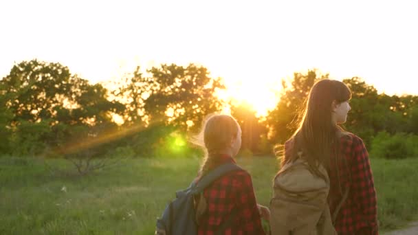 tourist girls on country road. Hiker Girl, teen girls travel and hold hands. children travelers. girls with backpacks are on country road in sun. concept of sports tourism and travel