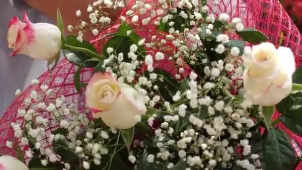 květiny jako dárek na dovolenou. Close-up. Kytice v rukou lidí z krásných květin a červených růží. Close-up.